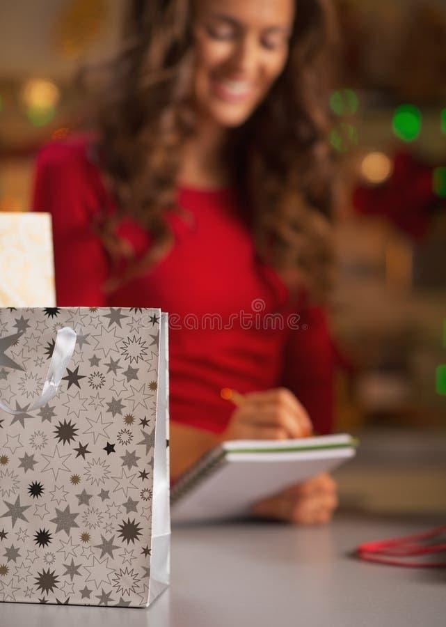 De close-up op het winkelen zak en vrouw die lijst controleren van stelt voor stock fotografie