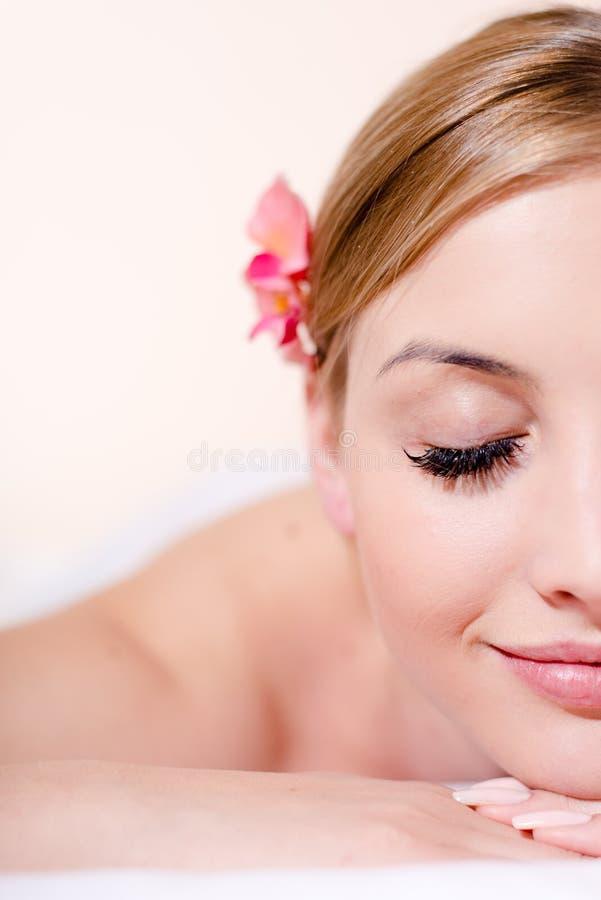 De close-up op mooie jonge blonde vrouw in kuuroordbehandelingen gelukkige het glimlachen ogen sloot op witte achtergrond royalty-vrije stock afbeelding