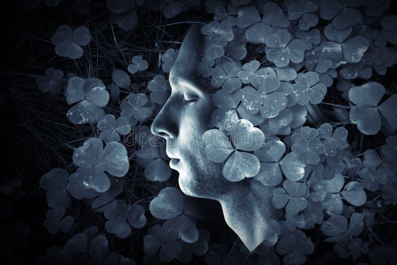De close-up profMale profileert en donkerblauw wild Oxalis-gras bos backgroundile portret van de jonge Kaukasische mens met geslo stock afbeeldingen