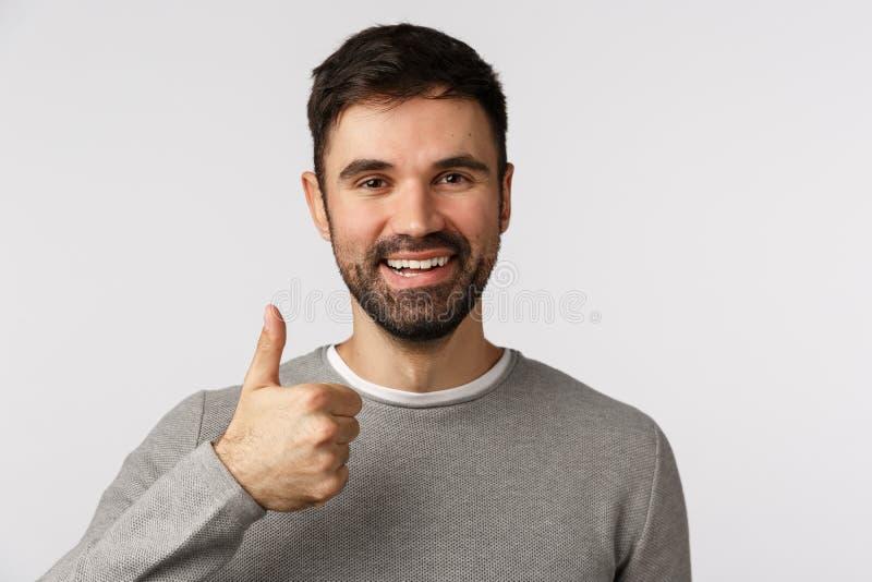 De close-up schoot betrouwbaar en blij glimlachend, gelukkige man met baard in grijs sweater, laat duim-up zien geven goedkeuring royalty-vrije stock fotografie