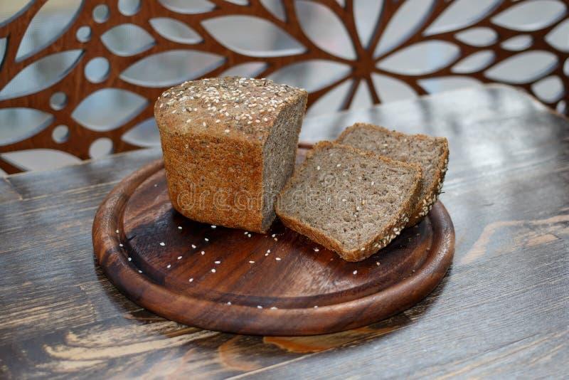 De close-up sneed ongedesemd brood op ronde scherpe houten raad royalty-vrije stock foto