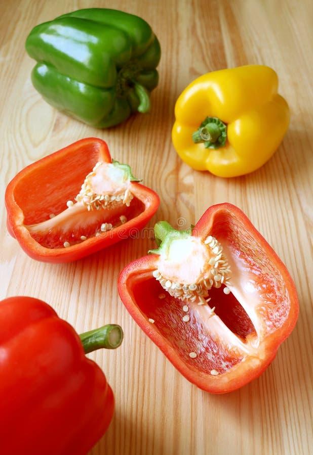 De close-up sneed Rode Groene paprika met Tricolor-Groene paprika's op Houten Lijst stock fotografie