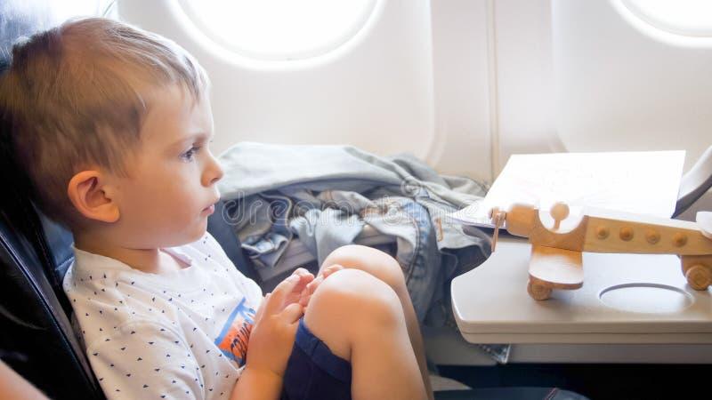 De close-up stemde foto van de leuke zitting van de peuterjongen in vliegtuig en het kijken op kleine stuk speelgoed tweedekker stock fotografie