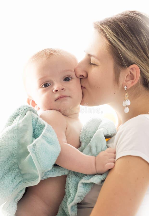 De close-up stemde portret van jonge houdende van moeder die haar babyzoon omvat in blauwe handdoek na het hebben van bad kussen stock afbeeldingen