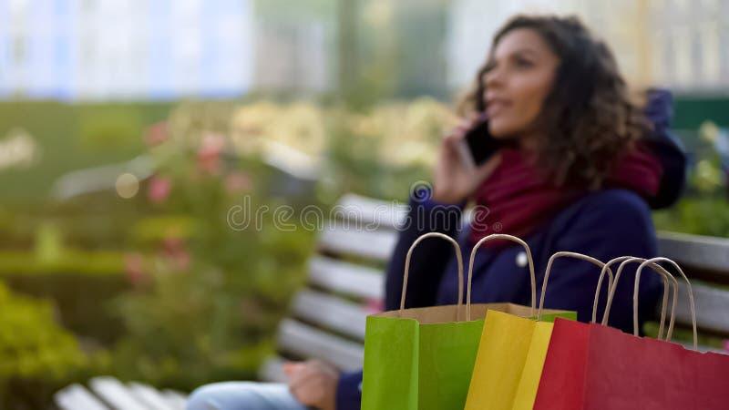 De close-up van aankopen, damebesprekingen over telefoon op achtergrond, schept over verkoop op stock foto