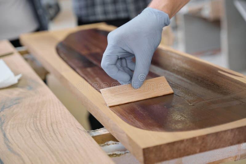 De close-up van arbeiders overhandigt het behandelen van houten plank met het be?indigen van beschermende dekking voor hout stock afbeeldingen