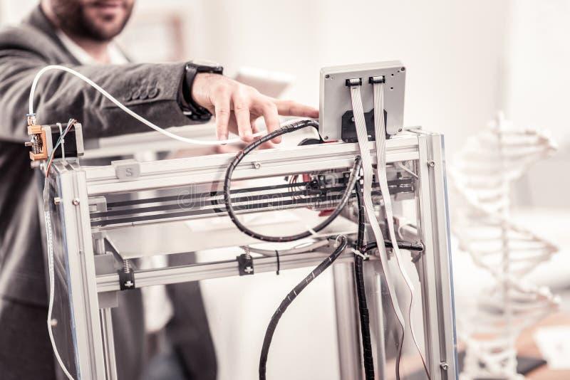 De close-up van bemant hand aanpassend professionele 3D printer stock afbeeldingen