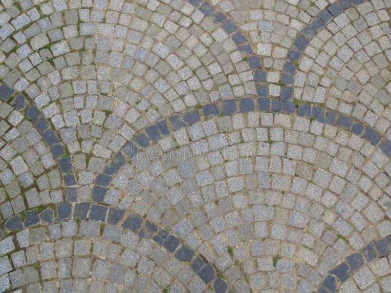 De close-up van a cobbled straat Grijze straatstenen cobblestones Betonmolens Ruimte voor tekst royalty-vrije stock foto