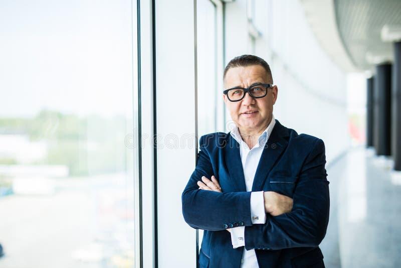 De close-up van een hogere zakenman met zijn wapens vouwde dichtbij panoramische vensters in een bureaubinnenland royalty-vrije stock afbeeldingen