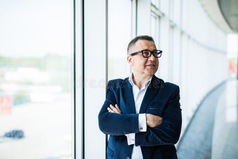 De close-up van een hogere zakenman met zijn wapens vouwde dichtbij panoramische vensters in een bureaubinnenland stock foto