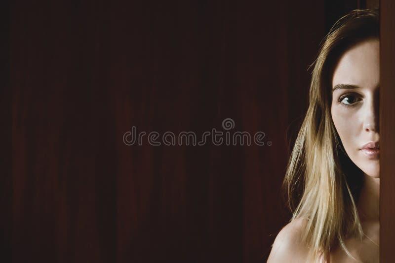 De close-up van een mooi meisje kijkt schuw terwijl het piepen achter een deur stock afbeelding