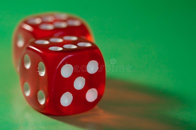 De close-up van een rood twee dobbelt met een het winnen aantal op het hoogste gezicht op een groene oppervlakte stock fotografie