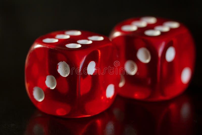 De close-up van een rood twee dobbelt met een het winnen aantal op het hoogste gezicht op een zwarte spiegeloppervlakte stock foto's