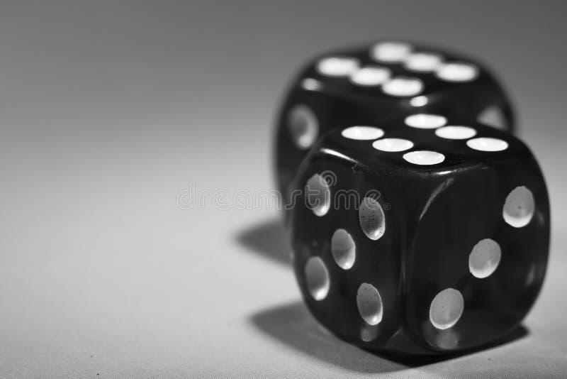 De close-up van een zwarte twee dobbelt met een het winnen aantal op het hoogste gezicht op een grijze oppervlakte royalty-vrije stock fotografie