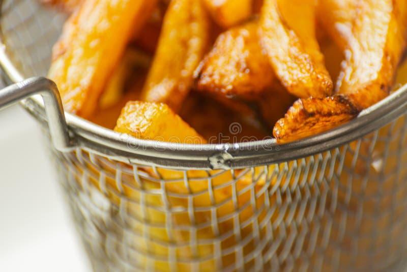 De close-up van gouden gebraden gerechten trof van verse vettige aardappels voorbereidingen, maar stock afbeelding