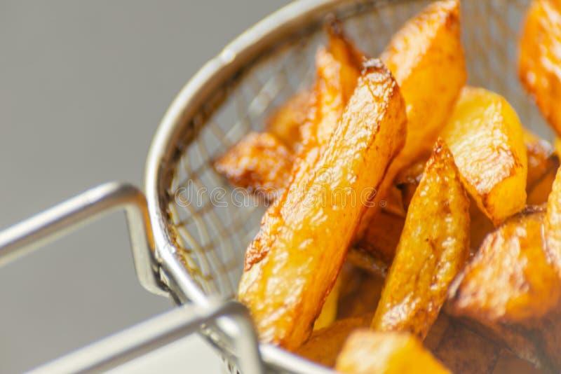 De close-up van gouden gebraden gerechten trof van verse vettige aardappels voorbereidingen, maar royalty-vrije stock afbeeldingen