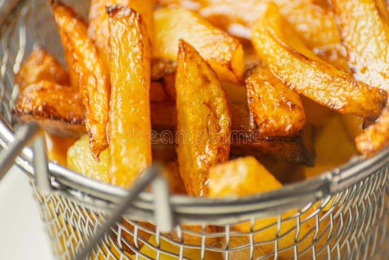 De close-up van gouden gebraden gerechten trof van verse vettige aardappels voorbereidingen, maar royalty-vrije stock foto