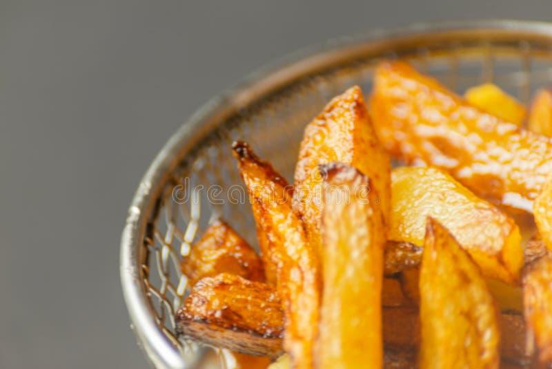 De close-up van gouden gebraden gerechten trof van verse vettige aardappels voorbereidingen, maar royalty-vrije stock afbeelding