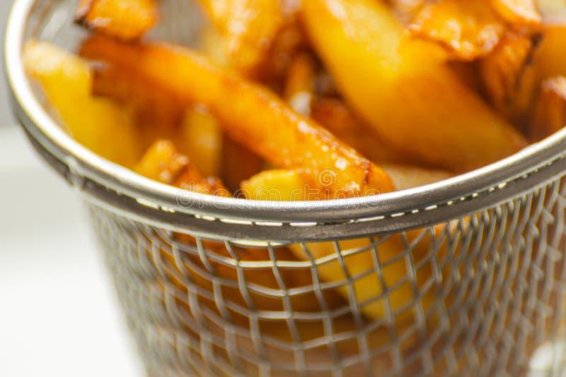 De close-up van gouden gebraden gerechten trof van verse vettige aardappels voorbereidingen, maar stock fotografie