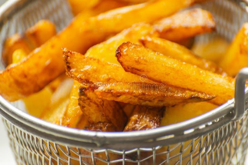 De close-up van gouden gebraden gerechten trof van verse vettige aardappels voorbereidingen, maar stock afbeeldingen
