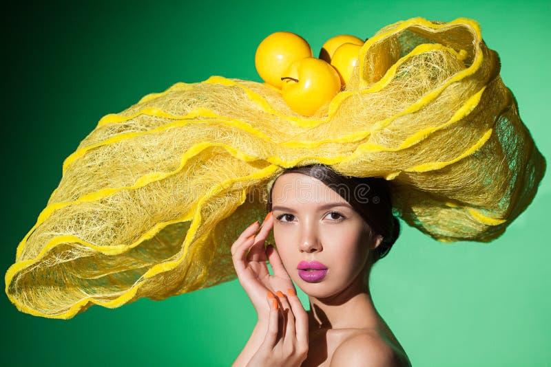 De close-up van het glamourportret van een jonge vrouw in gele hoed royalty-vrije stock afbeeldingen