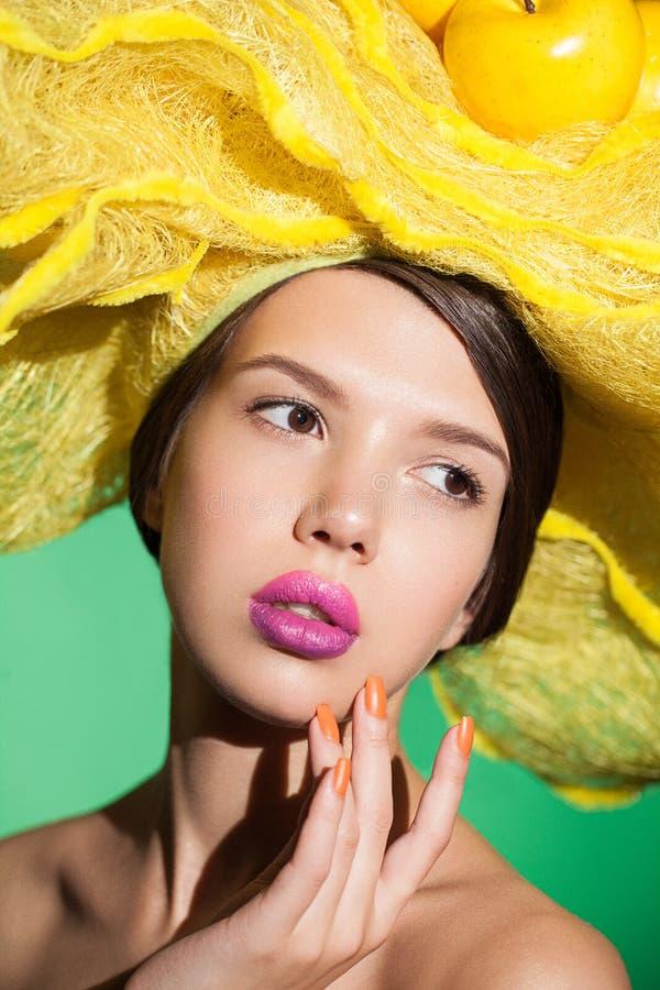 De close-up van het glamourportret van een jonge vrouw in gele hoed stock foto