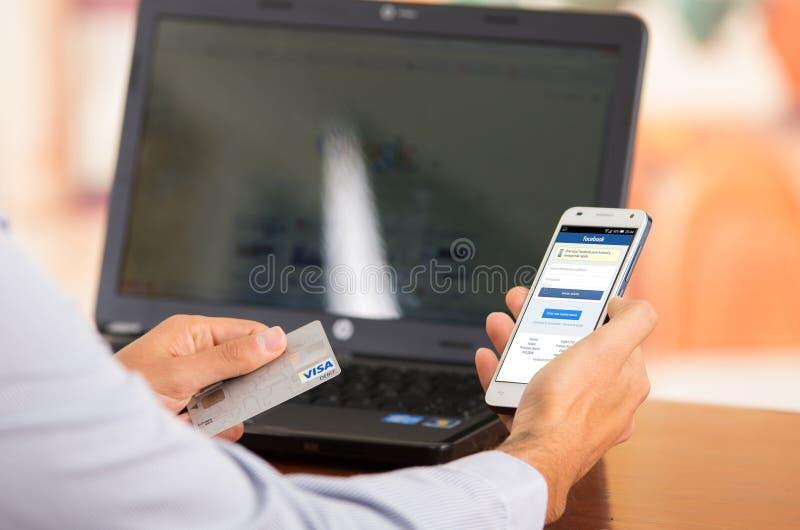 De close-up van jong bemant handen tegenhoudend smartphone met Facebook-zichtbare website, Visumkaart in andere hand met laptop stock afbeelding