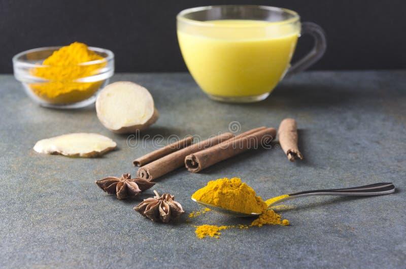 De close-up van lepelhoogtepunt van kurkumapoeder, kaneel, ster annise, gember en glaskop van kurkuma latte op de achtergrond com stock foto's