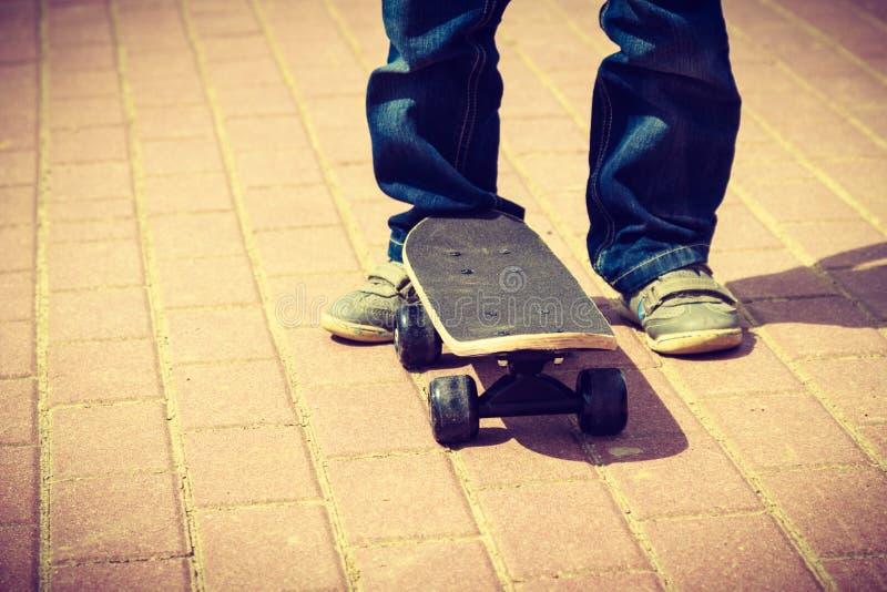 De close-up van Skateboarderbenen Jong geitje het met een skateboard rijden royalty-vrije stock fotografie