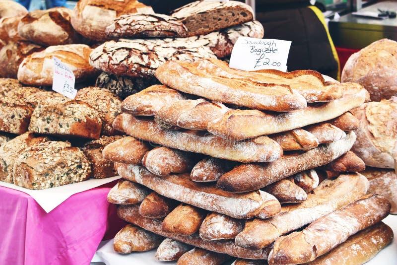 De close-up van stapel van verse Franse artisanale zuurdesembaguettes en geheel korrelgraangewas en pompoenzaad paneert de straat stock foto's