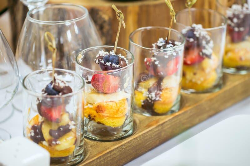De close-up van de suikergoedbar Zoete die Stukken van aardbei, druiven met kokosnoot het scheren en chocolade als canape op word stock foto