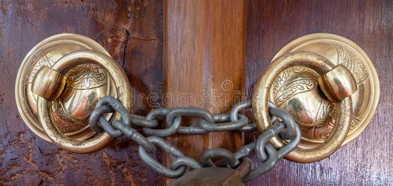De close-up van twee antieke kloppers van de koper overladen deur over een oude houten overladen deur sloot met geroeste ketting royalty-vrije stock afbeeldingen