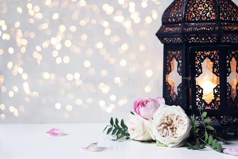 De close-up van uitstekende zwarte Marokkaanse, Arabische lantaarn, gloeiende kaars, groene takken, nam bloemen en bloemblaadjes  stock afbeeldingen