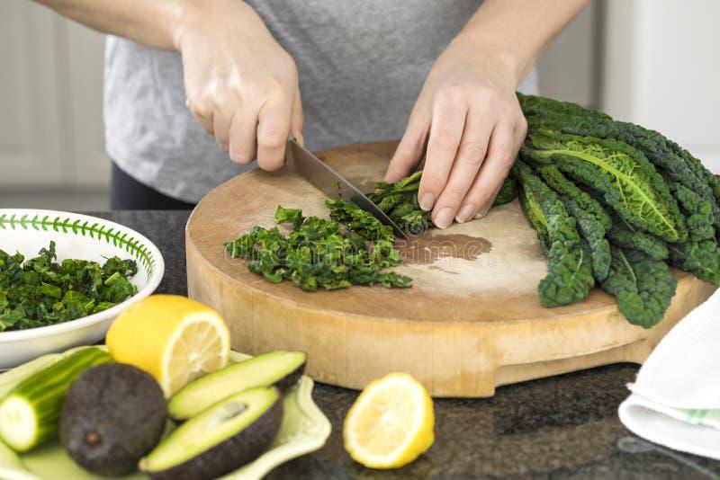 De close-up van vrouw ` s overhandigt kokende groentensalade in de keuken stock foto