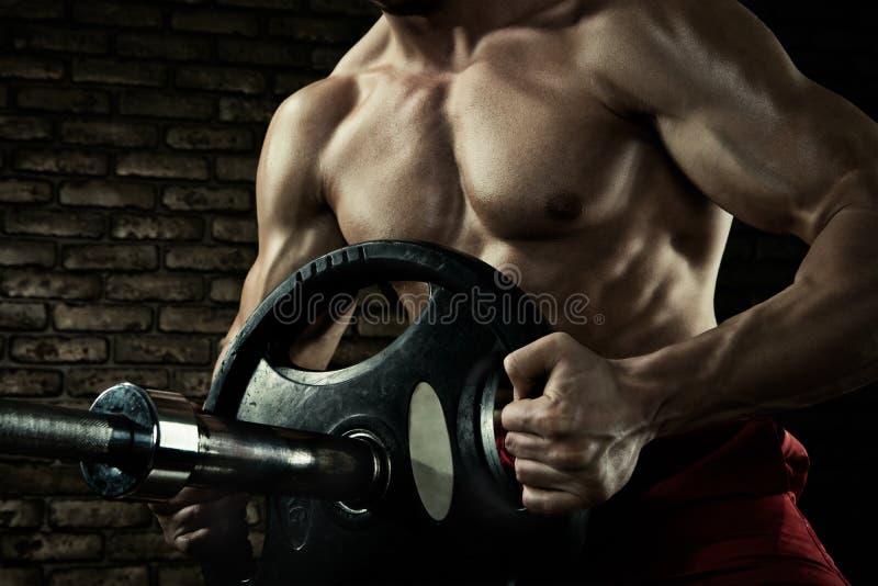 De close-upfoto van knappe bodybuilderkerel treft voorbereidingen om oefeningen met barbell in een gymnastiek te doen, barbell pl royalty-vrije stock afbeelding