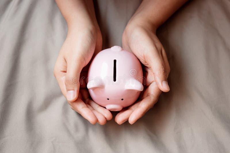 De close-uphanden is Holdingsspaarvarken op Stoffenachtergrond, het Bedrijfsbankwezen van het Besparingsgeld en of Financieel Con royalty-vrije stock afbeeldingen