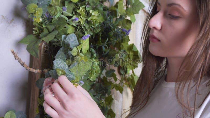 De close-upmening, een vrouwenbloemist verfraait een mooie houten photozone met bloemen stock afbeelding