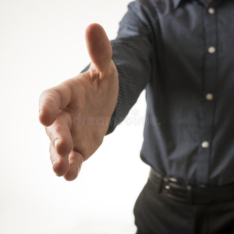 De close-upmening van een zakenman die van hem aanbieden dient een handdruk in royalty-vrije stock afbeelding