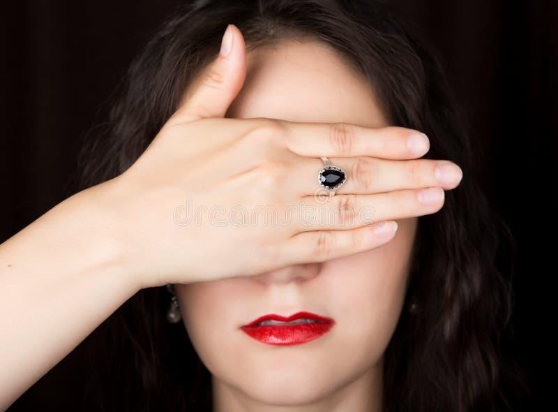 De close-upvrouw kijkt recht in de camera op een zwarte achtergrond lachende vrouw die haar ogen behandelen met haar hand royalty-vrije stock afbeelding