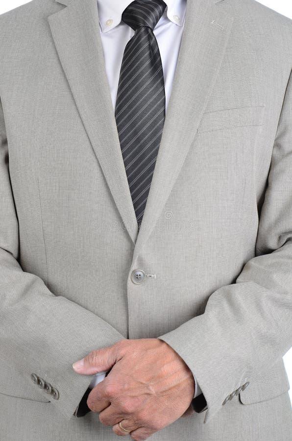 De close-upzakenman in een lichtgrijs kostuum en de grijze gestreepte band met handen clasped vooraan, is de torso slechts mens o stock afbeeldingen