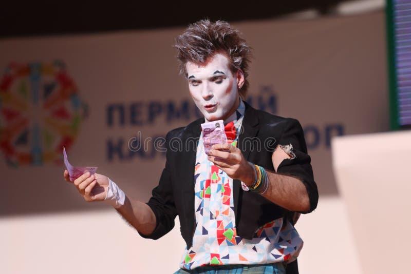 De clown houdt geld op openluchtstadium stock foto