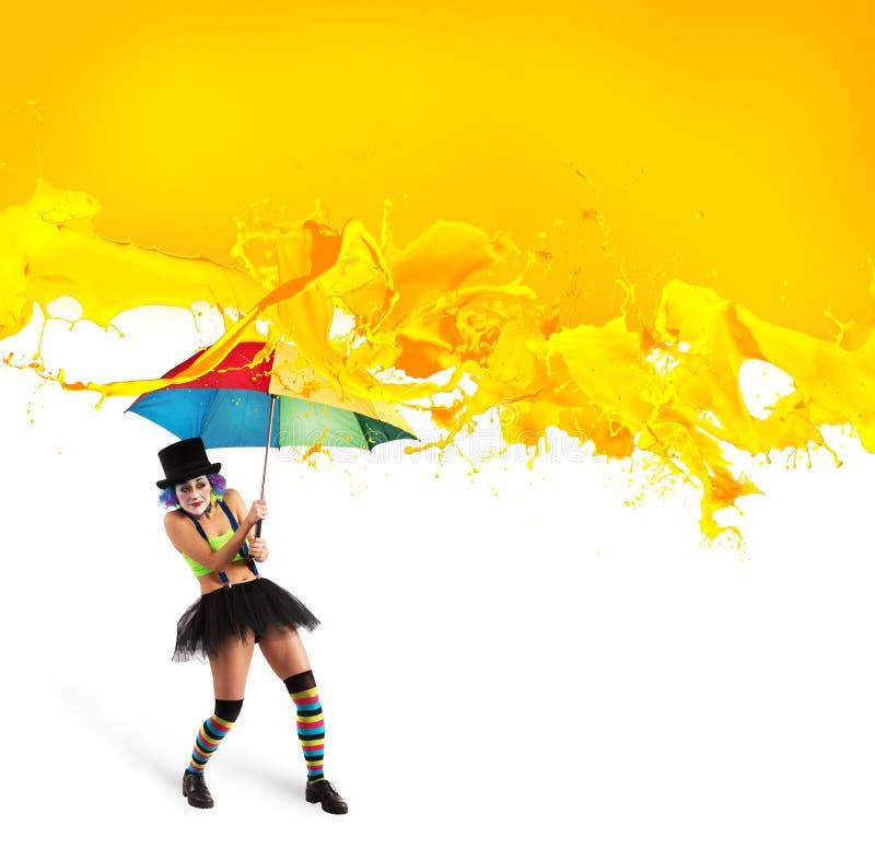 De clown met paraplu behandelt zich van gele kleurendalingen stock foto's