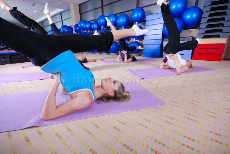 De club van de gezondheid: vrouwen die het uitrekken en aerobics doen zich royalty-vrije stock afbeeldingen