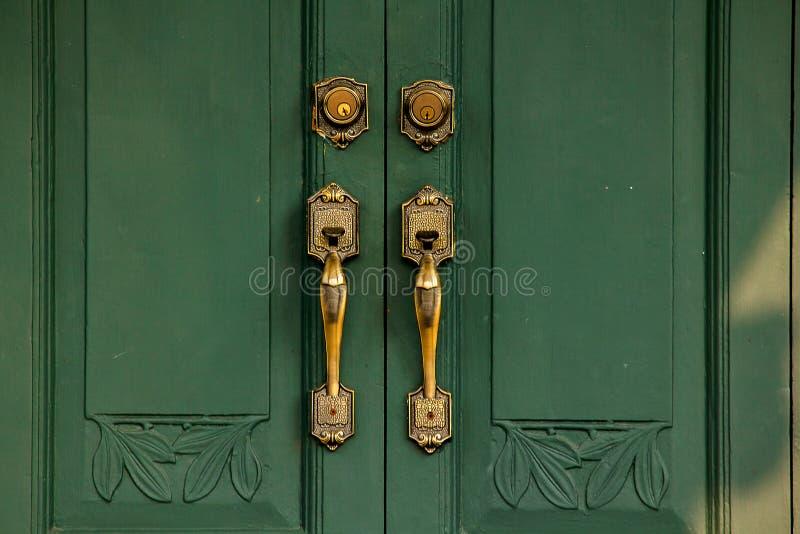 De cobre amarillo viejo de los tiradores de puerta en la puerta verde foto de archivo libre de regalías