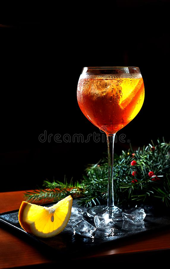 De cocktail van Aperolspritz met oranje plakken en ijsblokjes met Kerstmisspar vertakt zich op zwart dienblad op donkere achtergr stock foto's