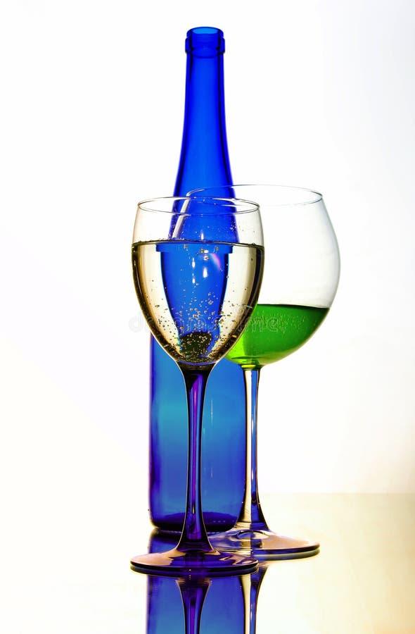 De cocktail van de glaslikeur met blauwe fles stock afbeeldingen