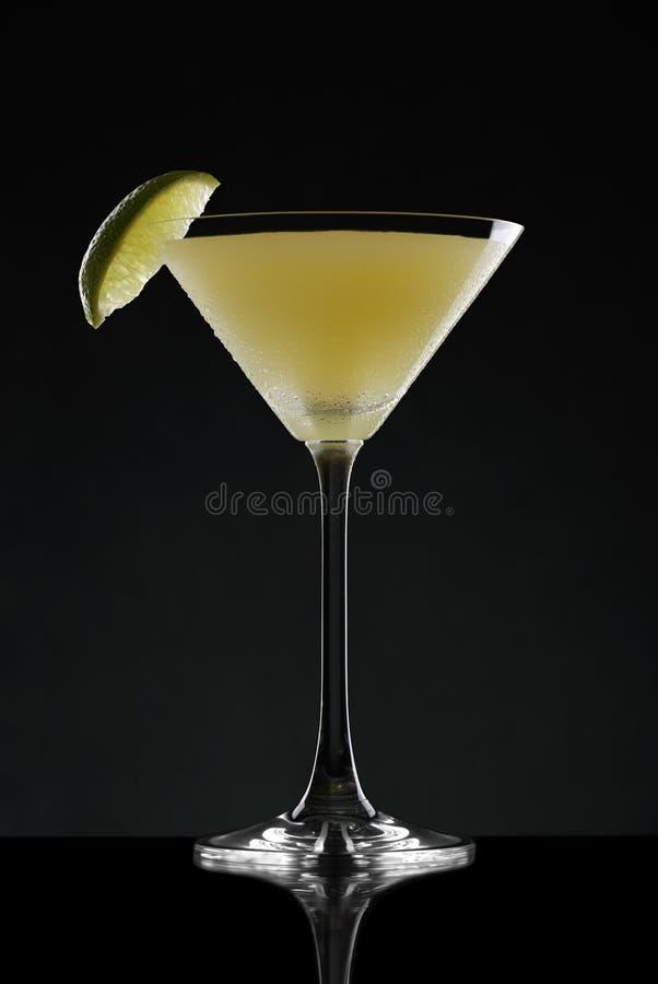 De cocktail van Margarita, met sterke hoogtepunten, en een kalkwig op een donkere achtergrond stock fotografie