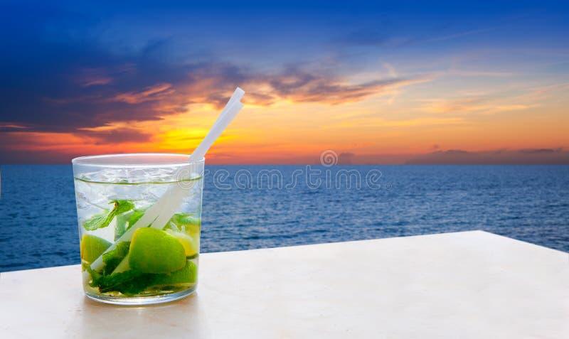De cocktail van Mojito op een gouden hemel van het zonsondergangstrand stock foto