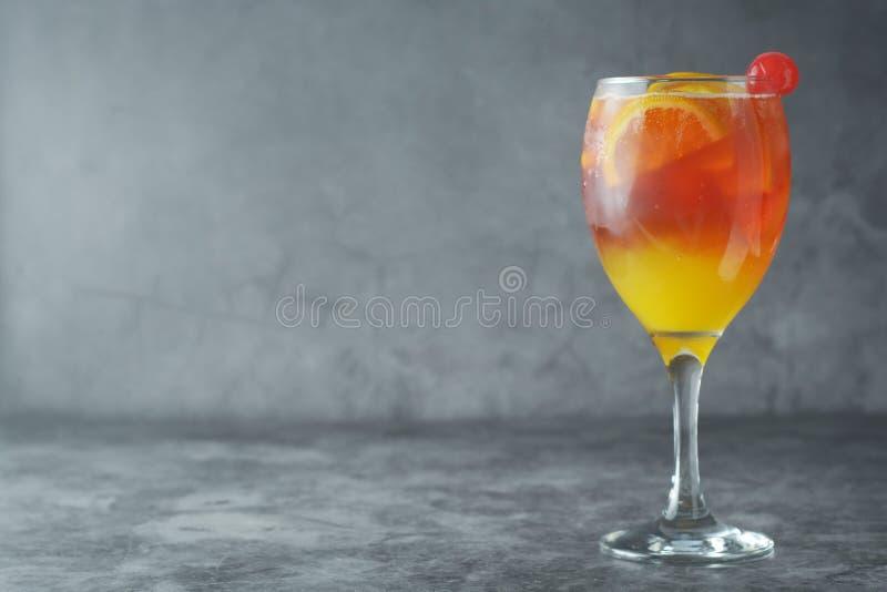 De cocktail van de zomer Jus d'orange met munt, syrop, fruitplakken en kers met ijs Donkere achtergrond stock foto