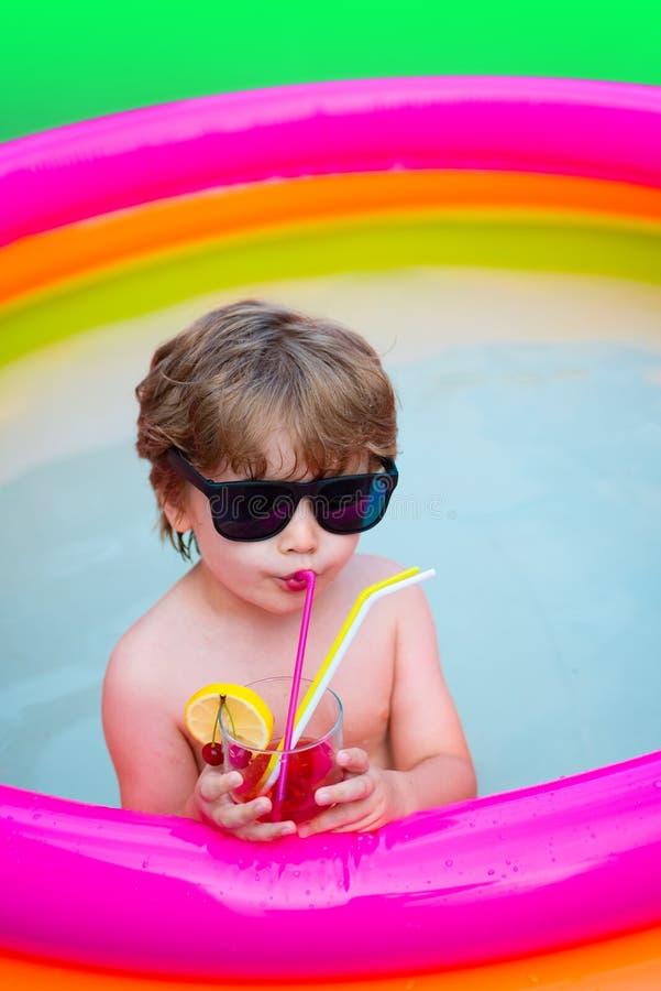De cocktail van de zomer Vakantie De vakantie van de zomer Het kind drinkt kleurrijke cocktail in zonnebril Pleziertoevlucht cock stock foto's